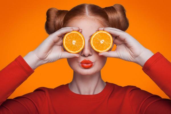 Young beautiful fashion model with orange. studio shot.